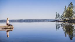 Nainen istuu laiturilla katsomassa Näsijärven maisemaa. Kuva: Laura Vanzo / Visit Tampere