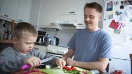 Mies ja poika pilkkomassa vihanneksia.