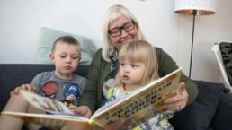 Arja Pärssinen lukee sohvalla kirjaa lapsille.