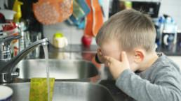 Poika pesemässä kasvojaan vesihanan alla.