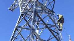 Sähköasentaja kiipeämässä voimalinjan pylvääseen