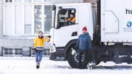Elina Tiira ja Soini Särkilahti seisovat biokaasukäyttöisen biojätteenkeräysauton edessä. Rami Saari istuu autossa kuljettajan paikalla.