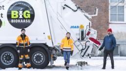 Rami Saari, Elina Tiira ja Soini Särkilahti seisovat biokaasukäyttöisen biojätteenkeräysauton edessä.