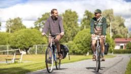 Kaksi pyöräilijää keskustelee ajaessaan kesäisellä pyörätiellä