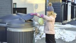 Tyttö laittaa roskapussia keräysastiaan talvella.