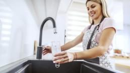 Nainen laskee vettä hanasta juomalasiin