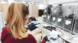 Tekstiilien lajittelua Nextiilissä, nainen selin punaisessa paidassa lajittelee
