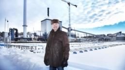 Jussi Laitinen seisoo Naistenlahden voimalaitoksen edessä. Maisema on talvinen, Jussi Laitisella on yllään ruskea karvahattu ja nahkatakki.