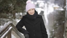 Sirkku Peltola nojaa kaiteseen Pispalan portaissa. Maassa on lunta, Peltola on pukeutunut vaaleanpunaiseen tupsulliseen pipoon sekä mustaan villakangatakkiin ja mustaan kaulahuiviin.