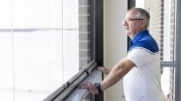 Juha Niemelä nojaa käsillään parvekkeen kaiteeseen ja katselee ulos.