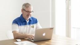 Juha Niemelä istuu pöydän ääressä ja näppäilee avattua tietokonetta.
