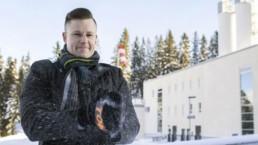 Samu Lepistö seisoo talvisella pihamaalla pukeutuneena villakangastakkiin ja huiviin. Hän läpsäyttää lapaskädet yhteen ja lumi pöllyää lapasten välistä.