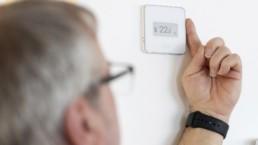 Juha Niemelä säätää asuntonsa lämpötilaa painamalla seinässä olevan termostaatin syrjää sormellaan.